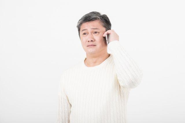電話で問い合わせをする男性